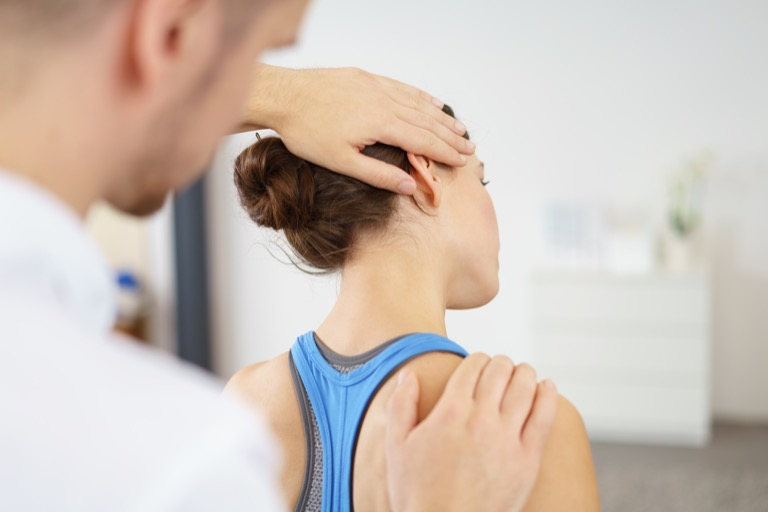 Practitioner examining a lady's shoulder