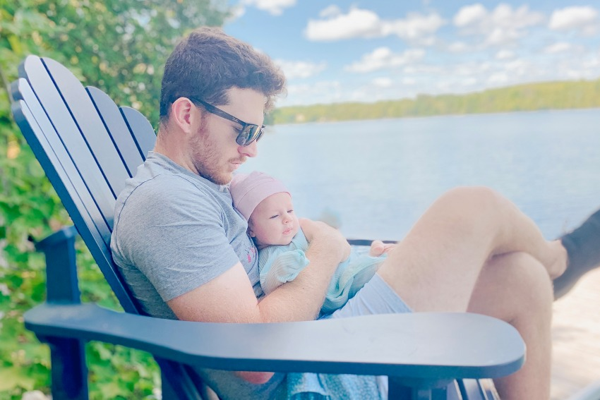 Dr Peter Wise sitting with daughter by lake