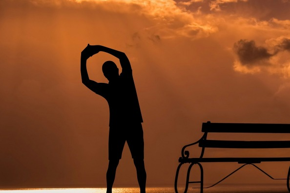 Man stretching at sunrise by ocean